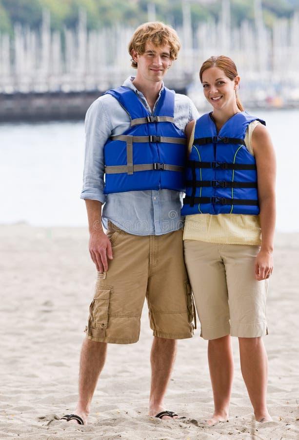 Couple wearing life jackets at beach royalty free stock photo