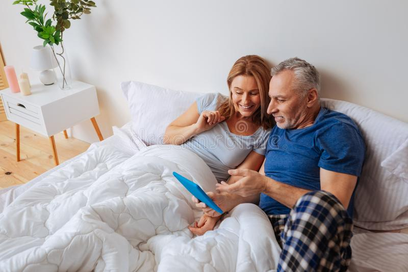 Couple wearing pajamas lying in bed and watching funny movie stock photos