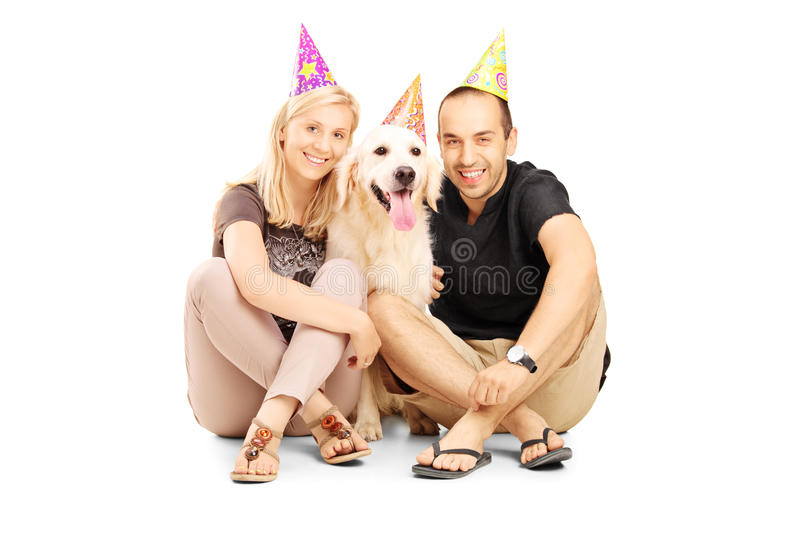 Couple wearing party hats with their dog seated on a floor. Heterosexual couple wearing party hats with their dog seated on a floor isolated on white background royalty free stock photos