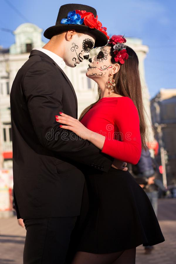 A couple, wearing skull make-up for. All souls day. Boy and girl sugar skull makeup.painted for halloween standing on the street. stock photo