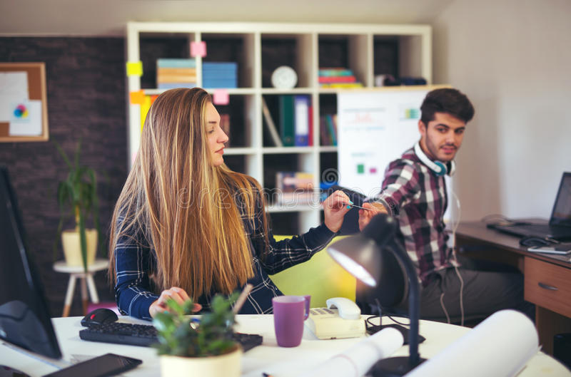 Couple of web designers working together at modern office. Using credit card royalty free stock photo