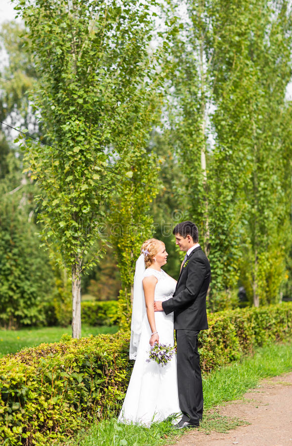 Couple in wedding attire with a bouquet of flowers, bride and groom outdoors royalty free stock photos