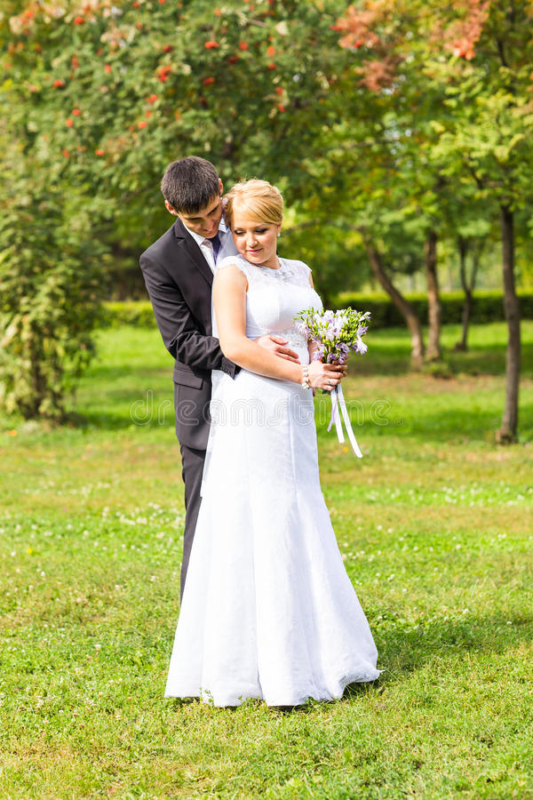 Couple in wedding attire with a bouquet of flowers, bride and groom outdoors stock photos