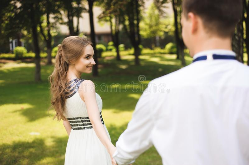 Couple in wedding attire is in the hands against the backdrop of the field at sunset, the bride and groom stock photography