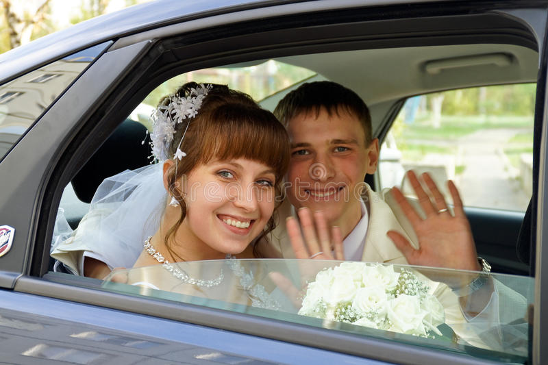 The couple in a wedding car. Beautiful newlyweds a wedding car stock images