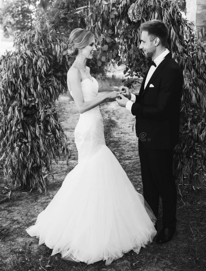 Couple in a wedding dress exchanges rings in the garden with an arch. black and white photo royalty free stock photos