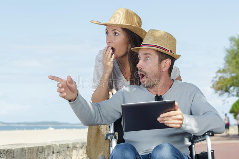 Couple in wheelchair looking surprised at women royalty free stock photography