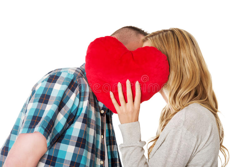 Couple whispering behind the pillow royalty free stock images