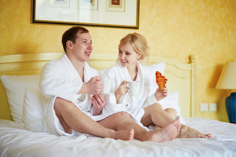 Couple in white bathrobes in bed, drinking coffee royalty free stock photo