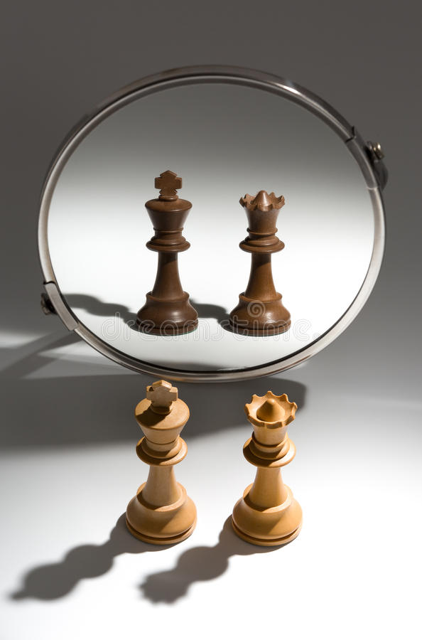 A couple of a white king and queen is looking in a mirror to see themselves as a black couple. stock images