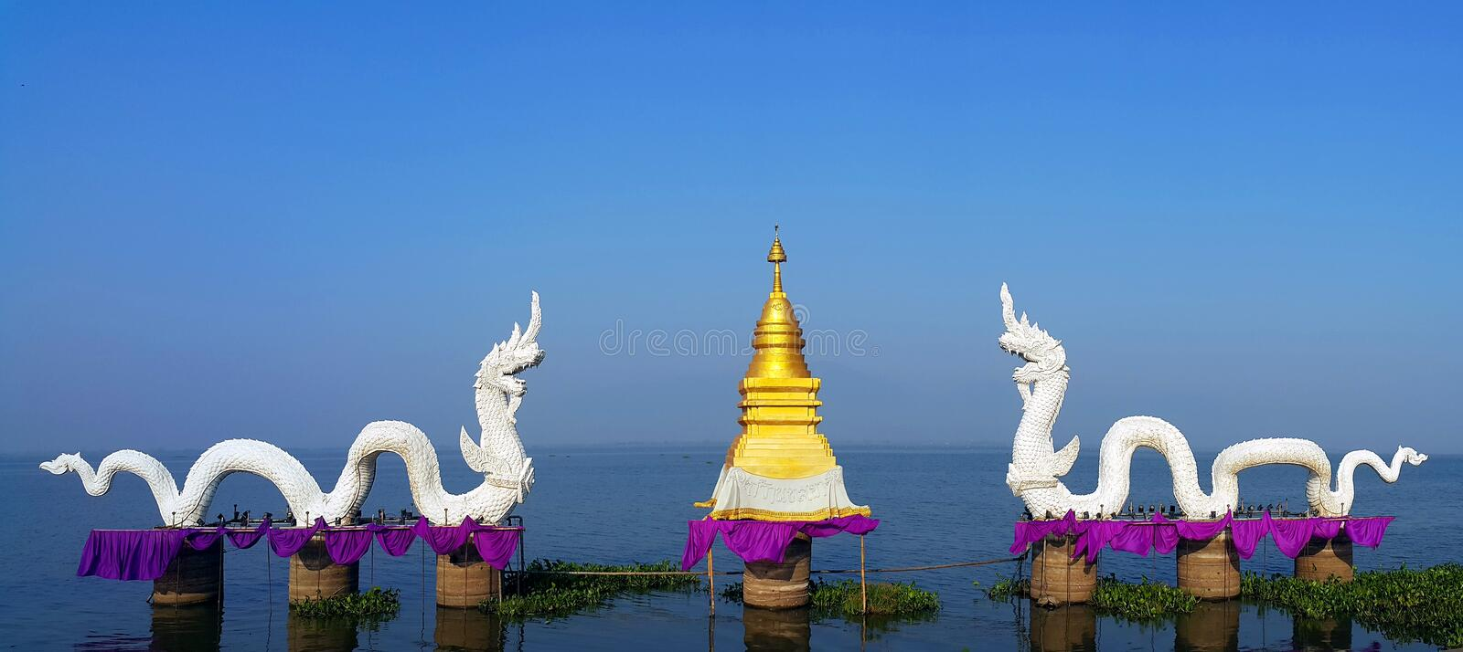Couple of white serpent king or king of naga statues with golen stupa at Kwan phayao, Th stock photos