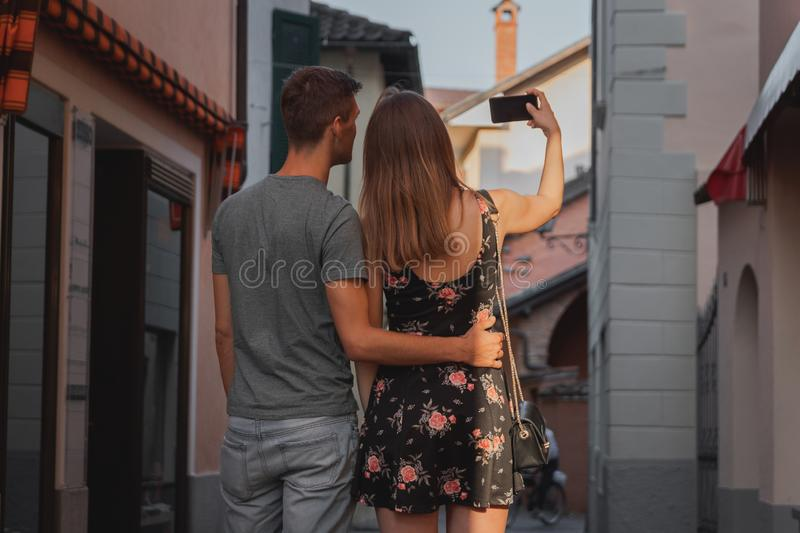 Young couple in love taking a selfie during shopping in an alley in ascona stock photography