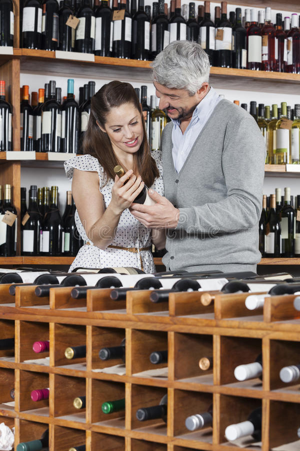 Couple With Wine Bottle Standing At Rack. Smiling couple with wine bottle standing at rack in shop stock photography