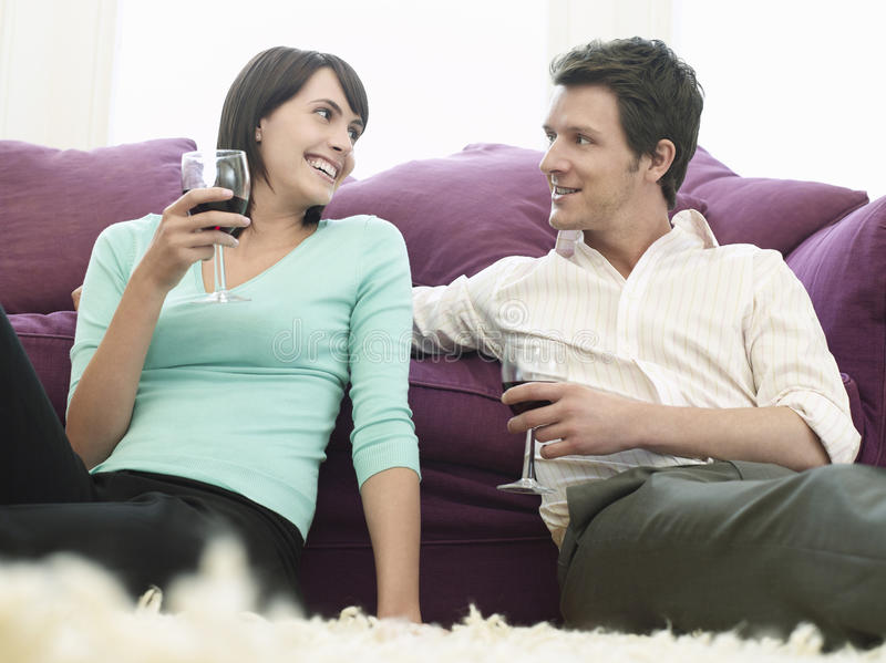 Couple With Wine Glasses Relaxing By Sofa royalty free stock photo