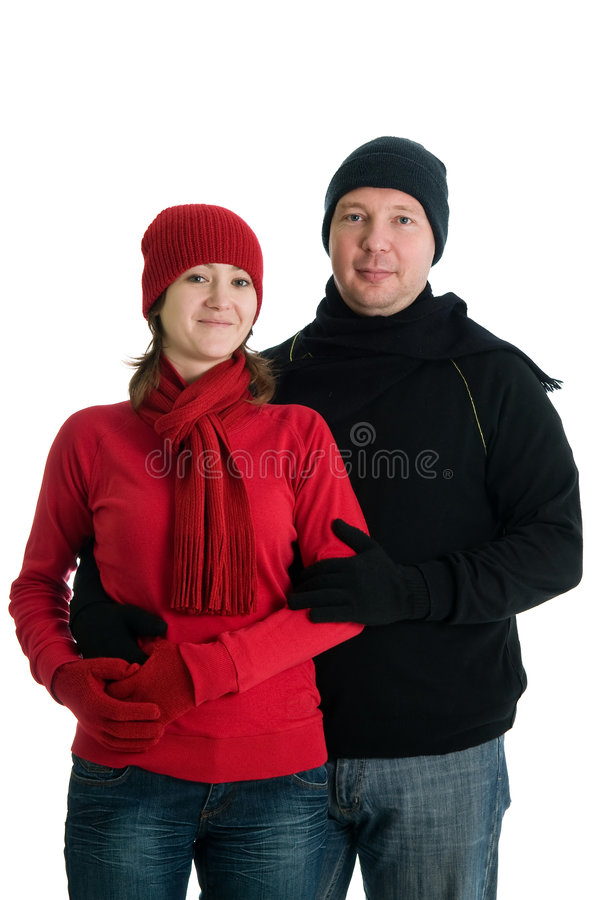 Couple in winter dress. Young couple in winter dress posing. Isolated over white stock photo