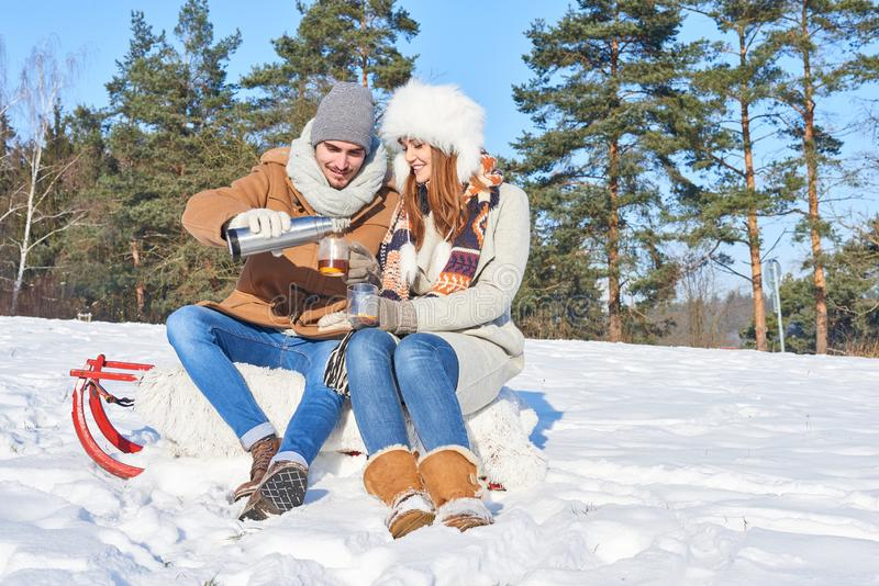 Couple in winter trip having a break stock photography