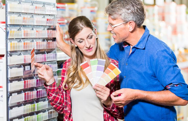 Couple choosing color of paint in hardware store. Couple, women and man, choosing color of wall paint in decoration department of hardware store stock photo