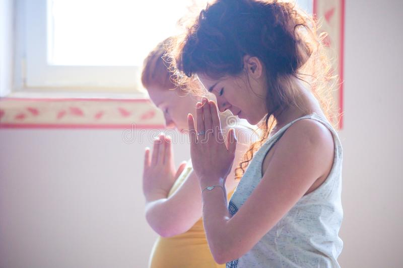 Couple of women on yoga class closeup of hands in namaste gesture indoor. Natural light royalty free stock photography