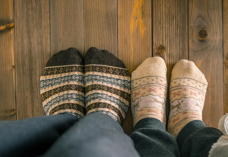 Couple with woolen socks sitting on wooden floor, winter cosy scene. A couple with woolen socks sitting on wooden floor, winter cosy scene stock photo