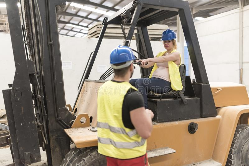 Couple of workers in industrial site. Pregnant woman driving for royalty free stock photography