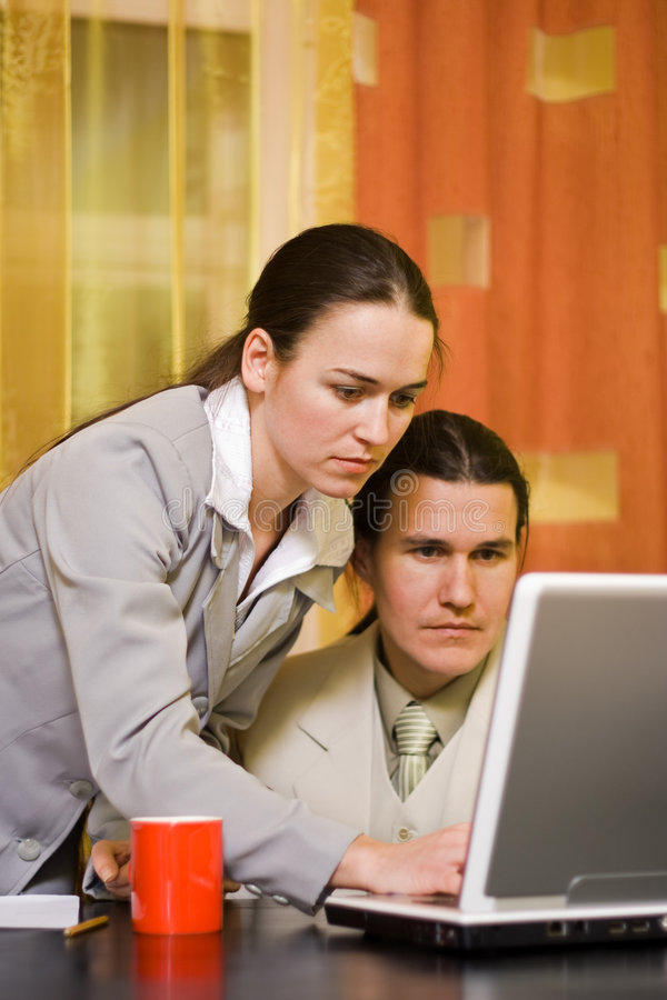 Couple working. Business couple working on laptop computer in office royalty free stock image