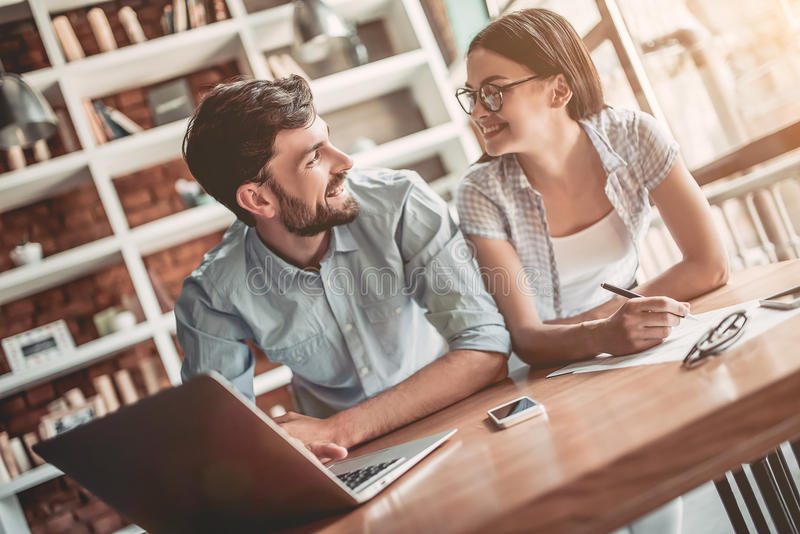 Couple working in cafe. Young couple is working in cafe. Discussing the latest news. Looking on each other and smiling royalty free stock image