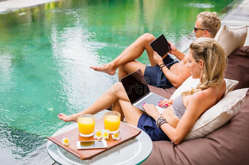 Couple working with computers while on vacation by the pool. Vacation concept stock photography
