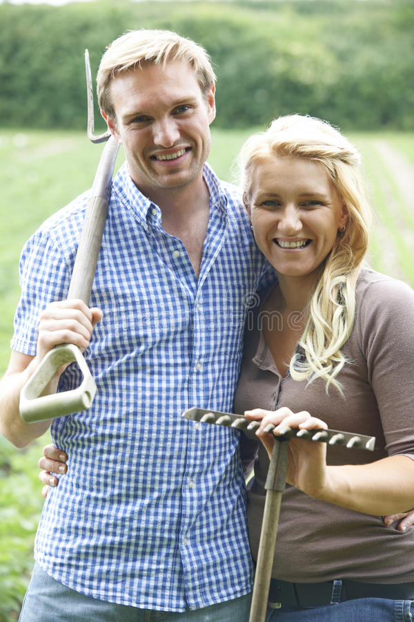 Couple Working In Field On Organic Farm. Young Couple Working In Field On Organic Farm royalty free stock images