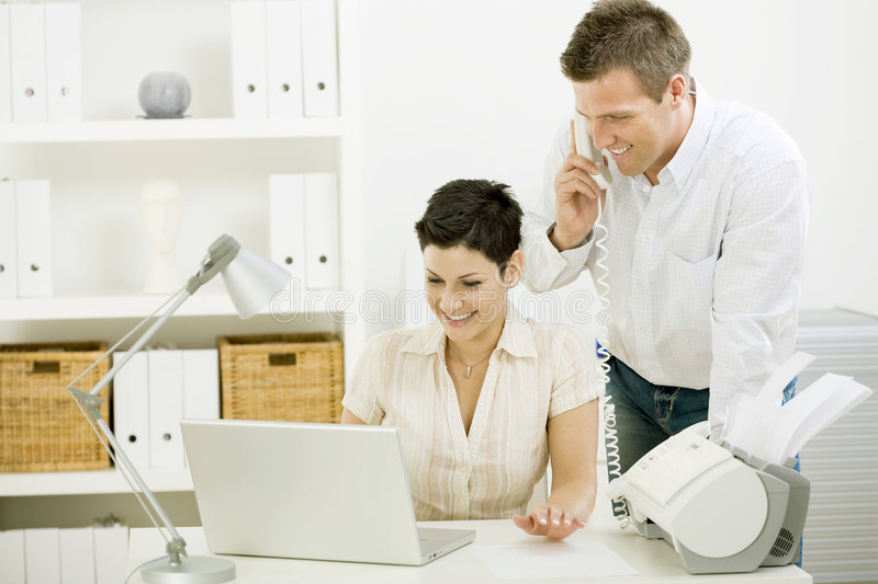 Couple working at home. Happy woman calling on phone at home office royalty free stock photos