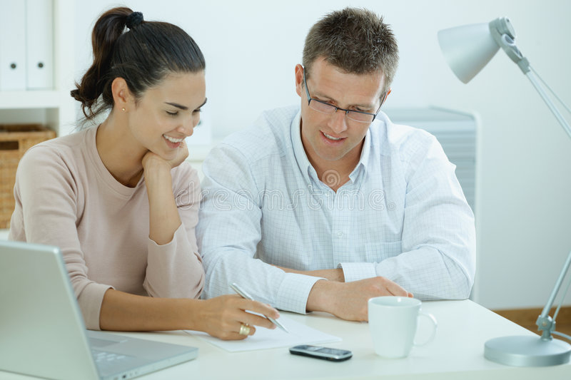 Couple working at home. Happy young casual couple sitting at desk working together at home office, smiling stock image