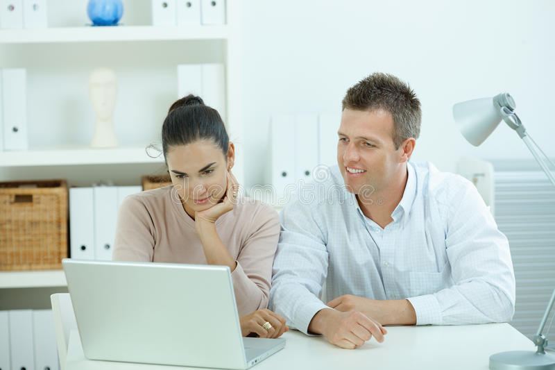 Couple working at home. Young casual couple sitting at desk working together at home office, smiling, happy, using laptop computer