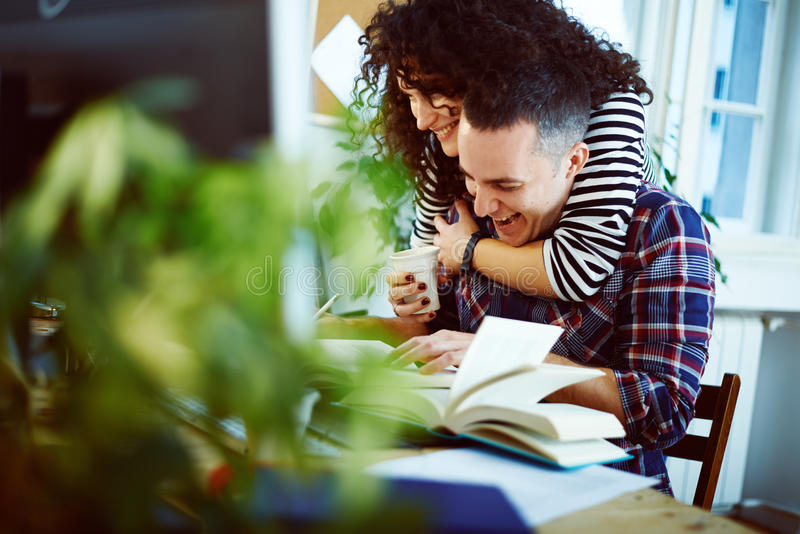 Couple working at home. She is embracing him stock photos