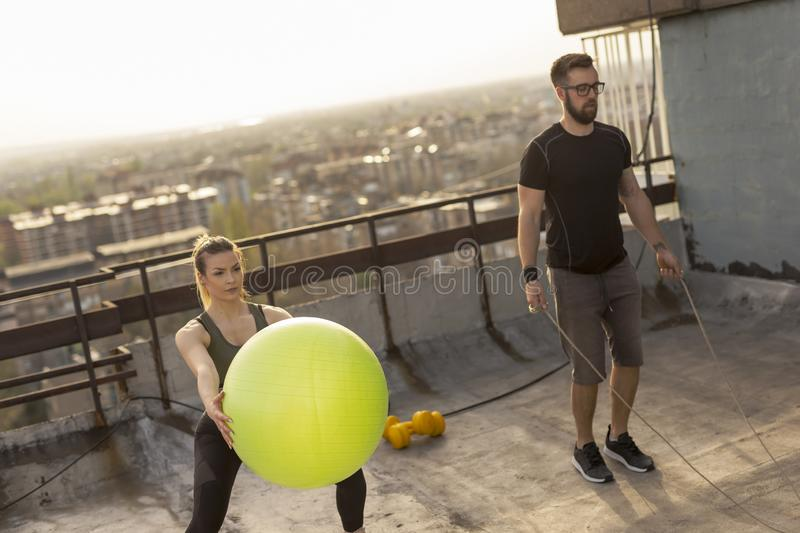 Couple working out. On a building rooftop terrace, doing jumping rope and pilates ball squats. Focus on the girl stock photo