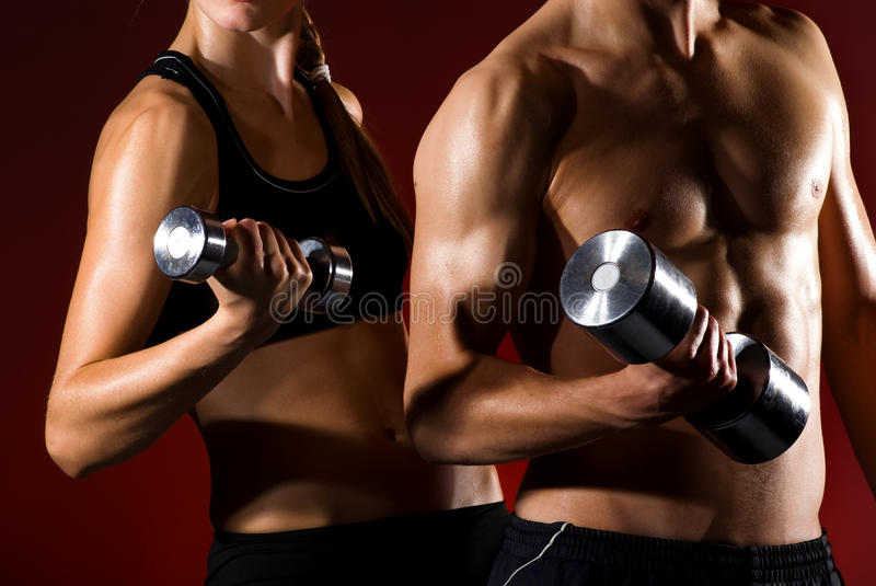 Couple working out with dumbbells. Strong young couple working out with dumbbells. Shot in studio on a red background royalty free stock image