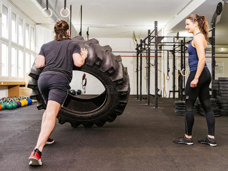 Couple working out with tire at crossfit gym stock images