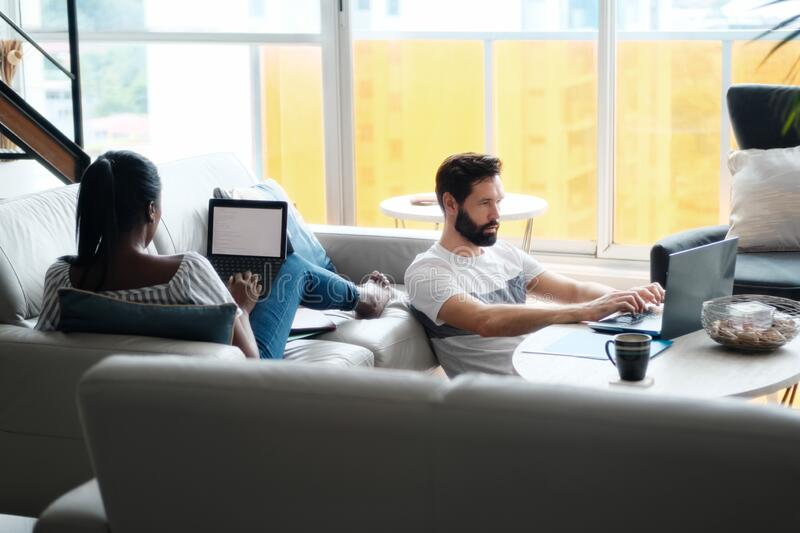 Couple Working And Playing With Laptop Computer At Home stock image