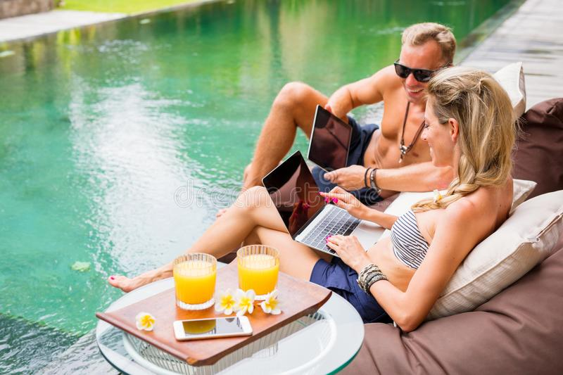 Couple working by the pool. Young couple working by the pool stock photo