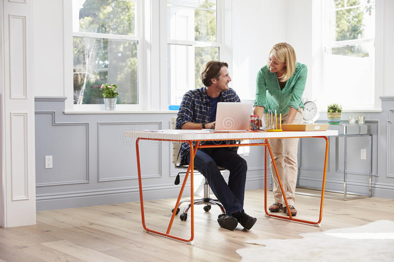 Couple Working Together At Desk In Home Office stock photo
