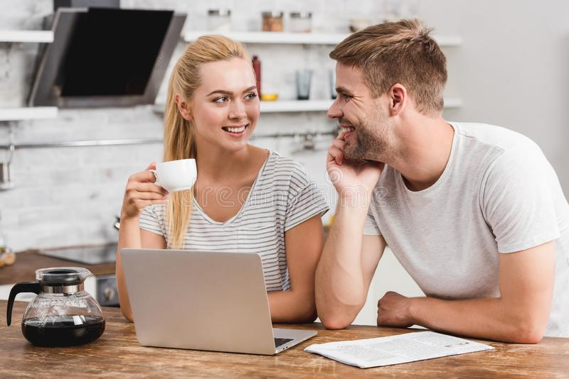 couple working together with laptop in morning and looking at each stock photography