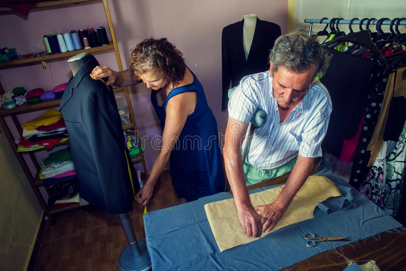 Couple working together on a tailoring. Mature couple working together on a tailoring royalty free stock photos