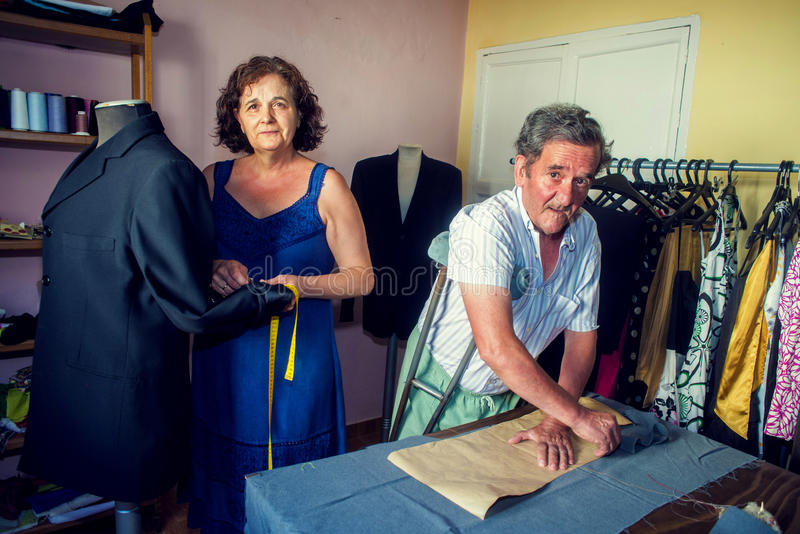 Couple working together on a tailoring. Mature couple working together on a tailoring stock photo