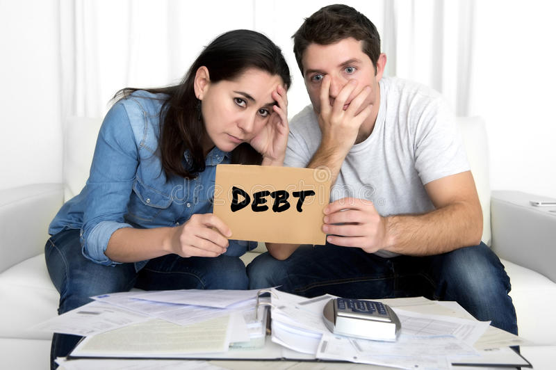 Couple worried need help in stress at home couch accounting debt bills bank papers expenses and payments. Young couple worried need help in stress at home living royalty free stock photography