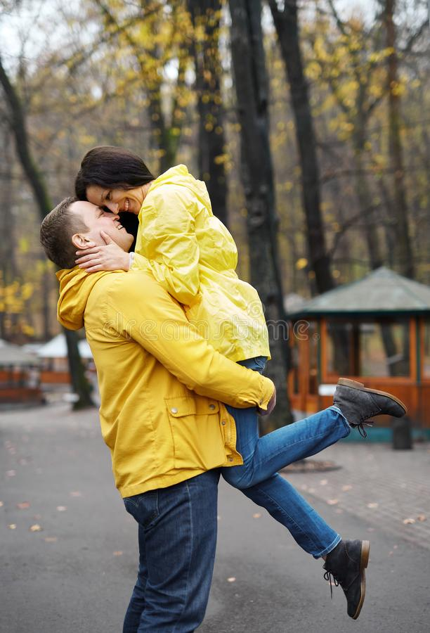Couple in yellow jackets embracing and kissing, walking in the autumn park. Happy young family spends time together. royalty free stock photos