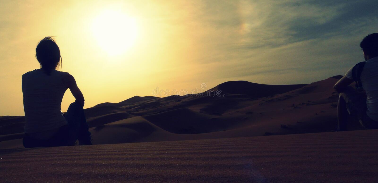 A couple of young adventurers sitting over a sand dune and enjoying an amazing sunset over the red dunes sea of Erg Chebbi. Morocco royalty free stock images