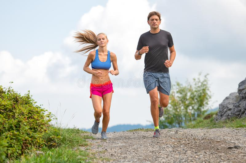 Couple of young athletes runs on dirt road stock images