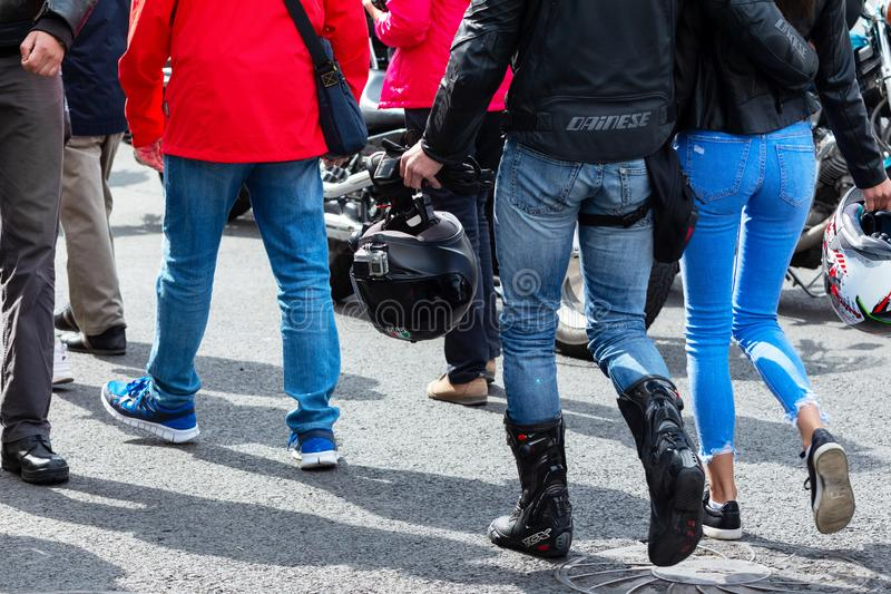 Couple of young bikers with helmets in their arms are hugging along the street. Slim legs of a girl in blue jeans next to a man stock photos