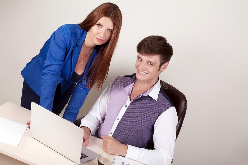 Couple of young designers working at modern office, two coworkers discussing fun project over a laptop, little team of businesspeo stock photo