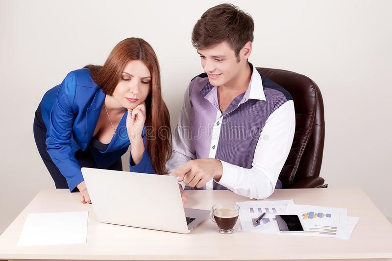 Couple of young designers working at modern office, two coworker stock photography