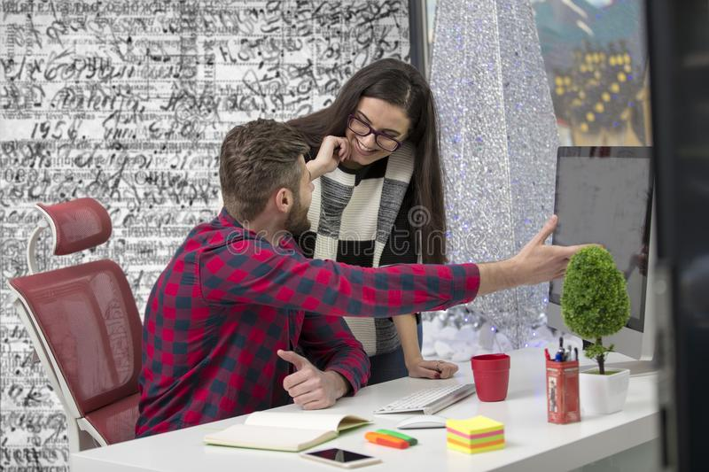 Couple of young designers working at modern office, two coworkers discussing fun project over a laptop, stock photos