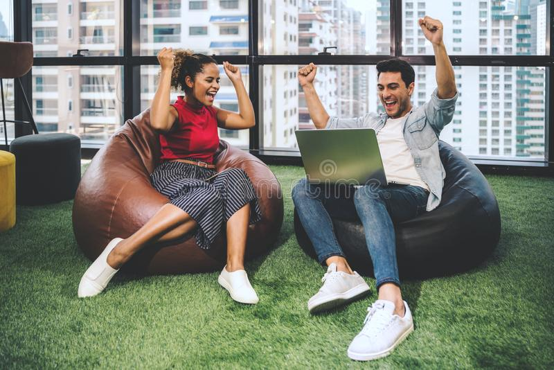 Couple of young designers working at modern office, two coworkers discussing fun project over a laptop, little team of royalty free stock images